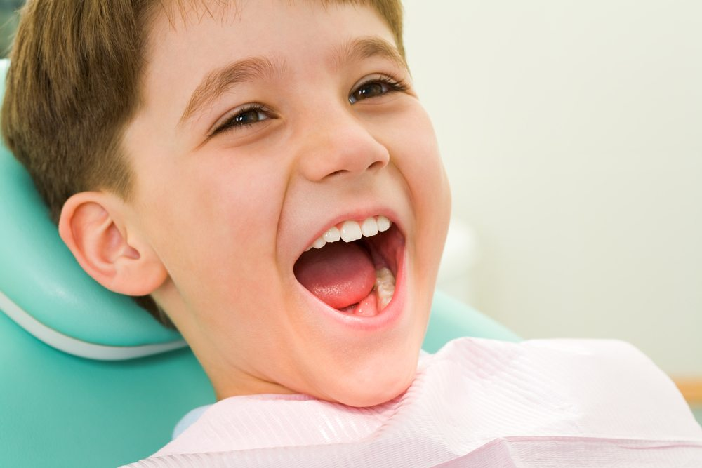 Little boy sitting in a dental chair with his mouth wide open showing his teeth
