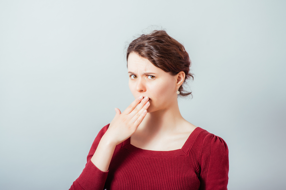 Woman with brown hair holds hand over her mouth because of bad breath