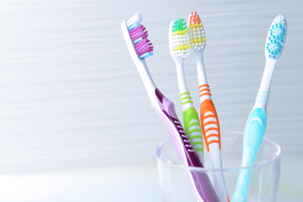 Four different colored toothbrushes in a glass